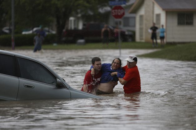 Marco Fairchild, left, and Gary Garza, right, help Sueann Schaller from her car after she drove it into floodwaters on Castleridge Dr. in the Westwood Village neighborhood off Military Dr. West in San Antonio, Texas, on Saturday, 25 May 2013. Photo: Lisa Krantz / San Antonio Express-News