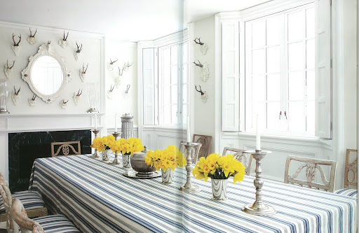 The dining room features Swedish accents from different time periods paired together–neoclassical chairs and modern linens.