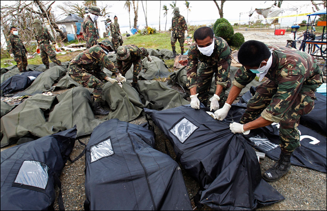 Soldiers zip up body bags after families have identified their relatives who perished during Typhoon Haiyan in Tacloban city, central Philippines, 13 November 2013. Photo: Edgar Su / Reuters