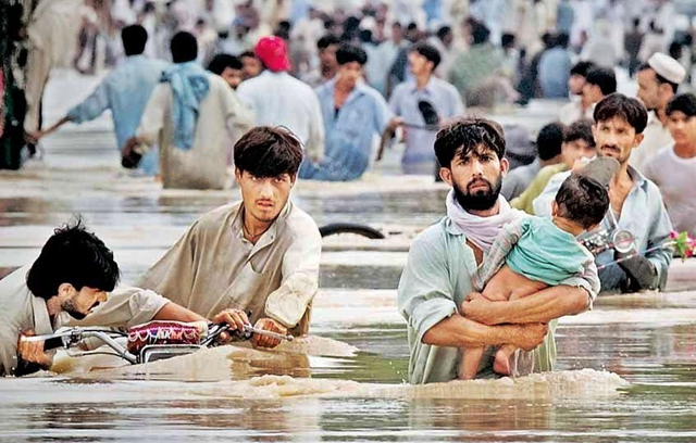Survivors wade through floodwaters in Pakistan, July 2010. stockmarkettoday.in