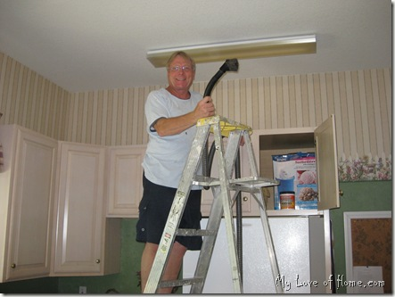 man cleaning light stripped wallpaper