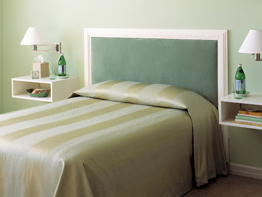 A built-in headboard made of velvet gives this bed a plush look. The side tables are simple and smart looking.