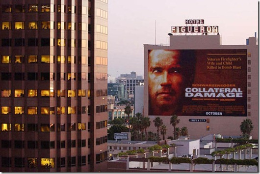 """A movie billboard advertising Arnold Schwarzenegge...LOS ANGELES, UNITED STATES:  A movie billboard advertising Arnold Schwarzenegger's new film """"Collateral Damage"""" about a bomb blast remains next to a downtown Los Angeles office tower, 12 September 2001. Warner Bros. today announced it was postponing the release of the film """"in light of yesterday's tragic events and out of respect for the victims and their families.""""  Disney also announced it was postponing the release of a film about an attack on US soil called """"Big Trouble.""""   AFP PHOTO/Lucy NICHOLSON (Photo credit should read LUCY NICHOLSON/AFP/Getty Images)"""