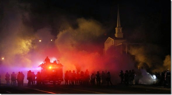 Tactical officers advance east on Chambers Ave. through clouds of tear gas as they try to clear protestors early on Wednesday, Aug. 13, 2014, in Ferguson.  It was the third night of unrest in Ferguson after the fatal police shooting of a teen on Saturday.