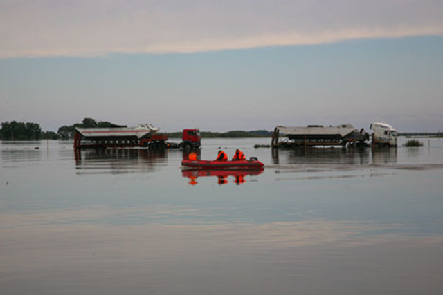 Residents of Russia's Far East steer an inflatable raft over floodwaters in the Amur River. In September 2013, over 60 communities with a combined population of almost 36,000 stll remained in the flood zone. Photo: RIA Novosti