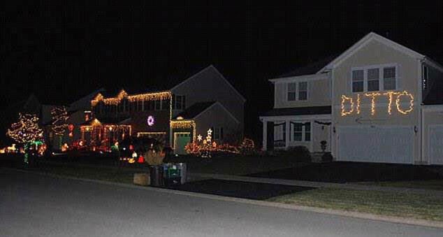 "A house with Christmas lights reading ""Ditto"" and an arrow pointing at the house next door which is covered in Christmas lights."