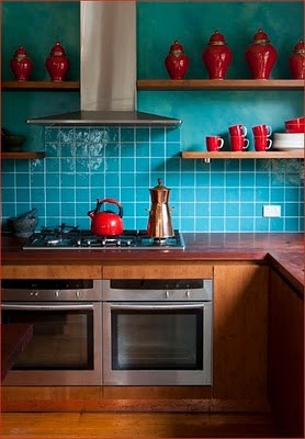 I love how the colors transition from emerald paint to turquoise tiles on this wall, and the collection of red vessels are so fun! (vi.sualize.us)