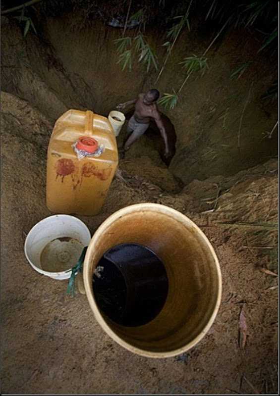 A man collects oil, in order to sell it on the black market.
