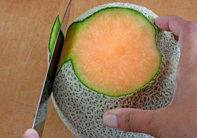 Slicing the skin of the melon in thick strips