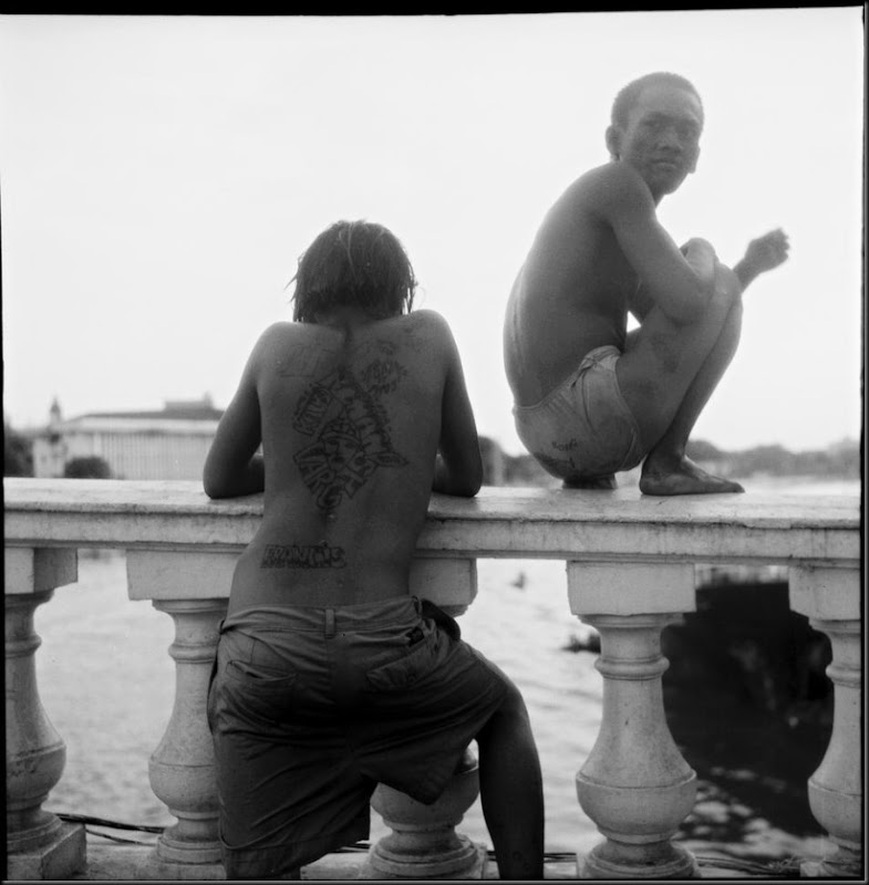 Two tattooed teenagers loiter on a bridge in Manila while asking for money from passersby to see them jump to the murky waters some twenty to thirty feet below.