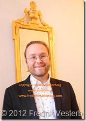 DSC02518 (1) Fredrik Vesterberg i mörk kavaj vid guldspegel. Med amorism
