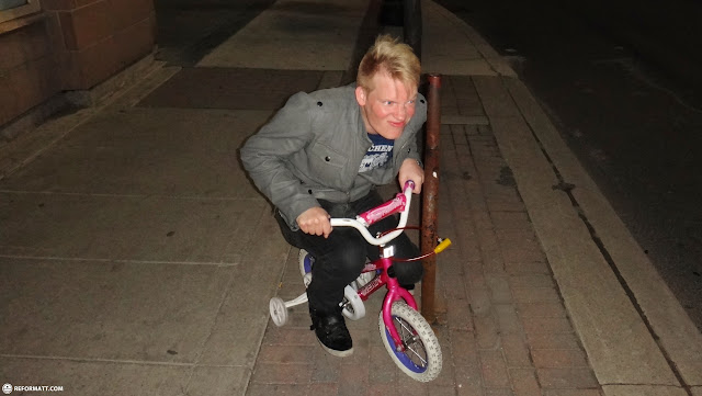 blonde guy on a child's bicycle at night in Hamilton, Ontario, Canada