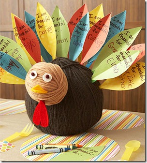 Thanksgiving kids table decorating and activity ideas--yarn turkey with paper feathers for kids to write what they're thankful for