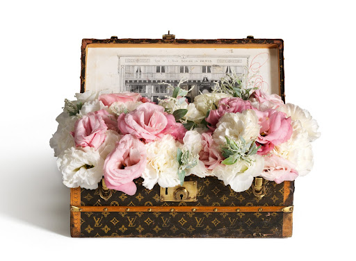 A flower trunk holding a mix of gorgeous blooms, complete with a zinc tray and monogrammed paper.