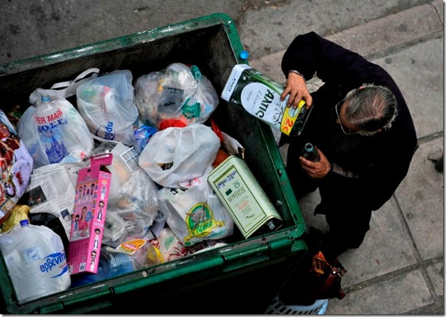 A man empties out the remains of an olive oil container from a trash bin in the northern Greek port city of Thessaloniki, Greece, Tuesday, Jan. 4, 2011. Welfare agencies and charity groups have warned of a spike in poverty and homelessness in Greece due to the effects of the financial crisis. (AP Photo/Nikolas Giakoumidis)
