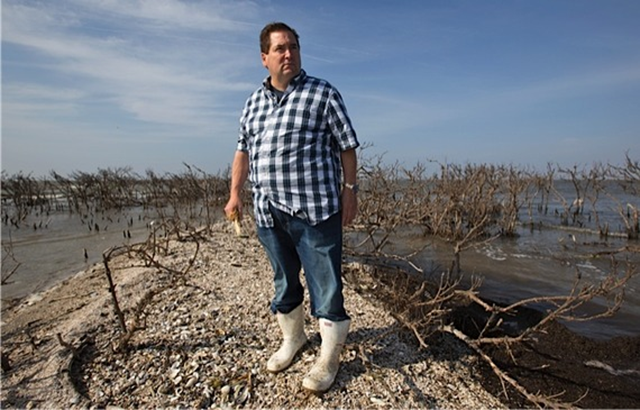 Billy Nungesser, president of Plaquemines Parish, Louisiana, stands on what remains of Cat Island, holding pelican bones, 18 April 2013. Three years after the BP Deepwater Horizon disaster, tar balls and oil sheen blight Gulf Coast. Photo: Julie Dermansky / The Atlantic
