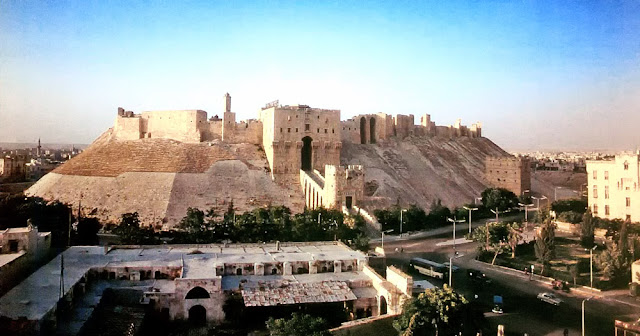 The Citadel at Aleppo. The most imposing building in Aleppo is the medieval Citadel, which rises high above the city.This natural, flat-topped mound was used in pre-lslamic times as a settlement and place of worship.The Ayyubid ruler al-Malik al-Zahir Ghazi (1186-1216) strengthened it into one of the best fortified military bases in Syria. He had a deep moat dug round the mound and filled with water, and built an imposing new entrance, which was flanked by two massive rectangular towers and could only be reached over a multiple-arch bridge. The Citadel was heavily renovated during the Mamluk period.The most significant addition was a sumptuous ceremonial hall, which the Mamluk governor Jakam min Iwad had built above the Ayyubid gate in 1406/07.