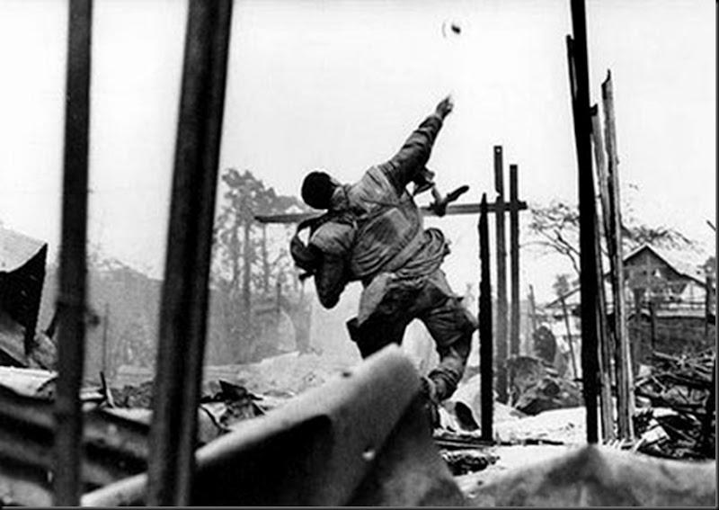 Viet-Nam, 1968. Marine américain lançant une grenade quelques secondes avant d'être blessé à la main gauche par un tir, offensive du Têt, Hué.