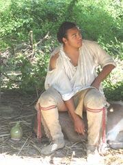 Plimoth Plant male indian sitting on log
