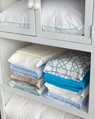 Keep sheet sets together with this trick. Tuck a sheet set inside one of its pillowcases, and then stack according to size (twin, full, queen, king) or by the room you use the sheets in (master bedroom, guest room.)