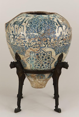 The Alhambra Vase | Origin:  Spain | Period: late 14th-early 15th century  Nasrid period | Details:  Mariano Fortuny, the famed textile and costume designer, bought the Freer Vase from a tavern in Granada. The bronze stand, inspired by the Fountain of the Lions at the Alhambra, was designed by Fortuny. The vase is missing its collar, neck, winglike handles, and lustered surface, but is a close cousin to other surviving Alhambra vases, including the vase known as the Alhambra Vase, now in the Museo de la Alhambra in Granada. Its present state only hints at its former appearance, as it must have been among the most magnificent of all of the late Alhambra vases. Its pleasing proportions are accentuated by the placement of an inscription band at its widest point; the contents of the inscription are unique among these vases. This inscription is autonomous, in that, it makes the vase speak in the first person. Like the inscription on the pyxis and other inscriptions that survive in stucco at the Alhambra palace, this one asks the viewer to contemplate the beauty of the object and its setting.   Inscriptions : Deer: Good health; Roundels: Good health. Central band: O thou onlooker who art adorned with the splendor of the dwelling / Look at my shape today and contemplate: thou wilt see my excellence / For I appear to be made of silver and my clothing from blossoms / My happiness lies in the hands of he who is my owner, underneath the canopy . | Type: Earthenware painted over glaze | Size: H: 77.2  W: 68.2  cm | Museum Code: F1903.206a-b | Photograph and description taken from Freer and the Sackler (Smithsonian) Museums.