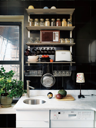 These black marble floor tiles from The Home Depot make a great and easy to clean backsplash.  The open shelving stocked with tools and supplies looks great against the dark tile.