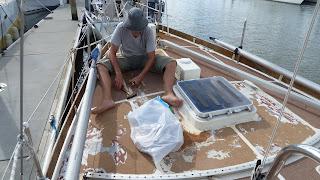 Noch im Wasser entfernen wir den Decksbelag und montieren nicht für die Überfahrt ins Trockendock benötigte Decksbeschläge ab.