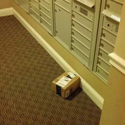 郵便ポストの前に放置された荷物