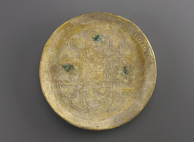 Dish | Origin:  Iraq | Period: 9th century  Abbasid period | Details:  Not Available | Type: Earthenware with molded decoration underglaze | Size: H: 2.8  W: 28.0  cm | Museum Code: F1957.23 | Photograph and description taken from Freer and the Sackler (Smithsonian) Museums.