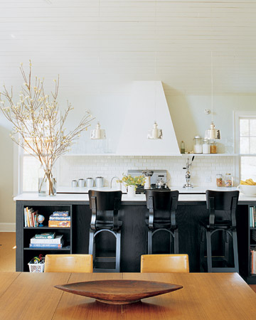 Black doesn't have to be heavy. This kitchen is bright and airy, but the black-painted island and chairs give it a central focus.