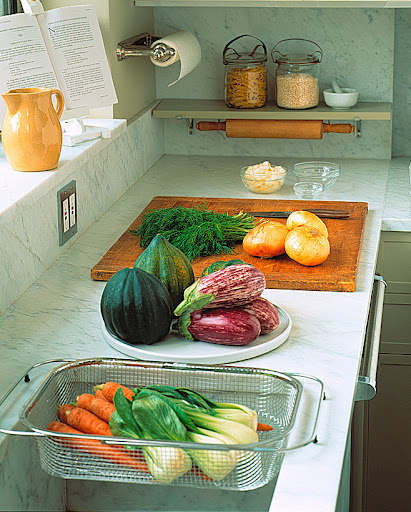 Create a perfect prep area by buying products that can be stored away when not in use. An improvised shelf keeps counters clean of rolling pins and dry-food canisters. A compact cookbook stand rests on the window ledge.