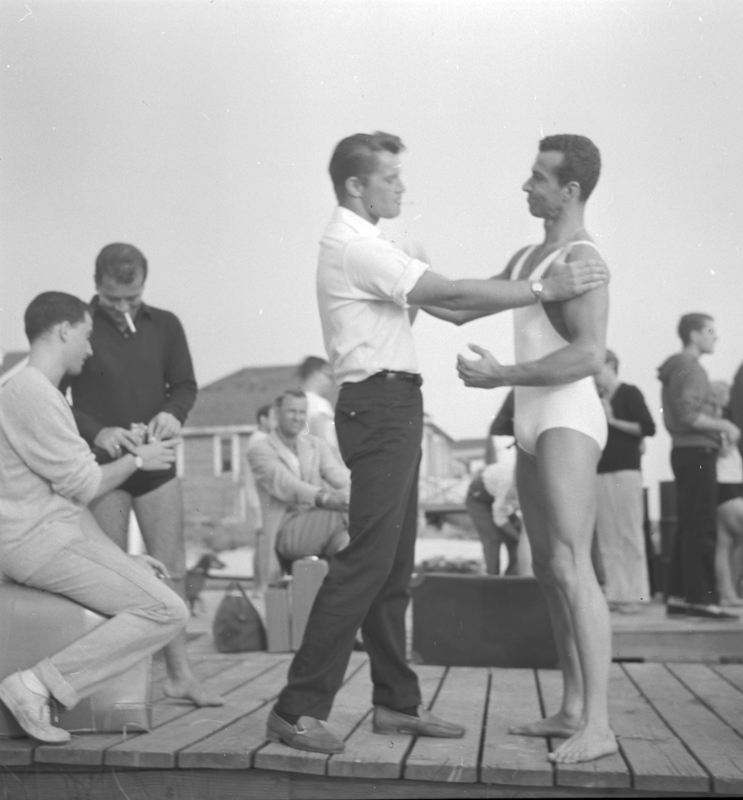 Model Christian William (Bill) Miller talks to Dev? Moderuage (bathing suit) on Fire Island. July 30, 1956.