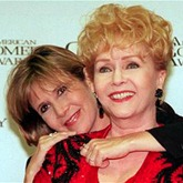 "REYNOLDS FISHER...Debbie Reynolds is hugged by her daughter Carrie Fisher backstage of the 11th annual American Comedy Awards in Los Angeles Sunday, Feb. 9, 1997. Reynolds was awarded a Lifetime Achievement Award at the ceremony. Both women are currently appearing in films, Reynolds in ""Mother,"" and Fisher is in the re-release of ""Star Wars."" (AP Photo/Rene Macura)"