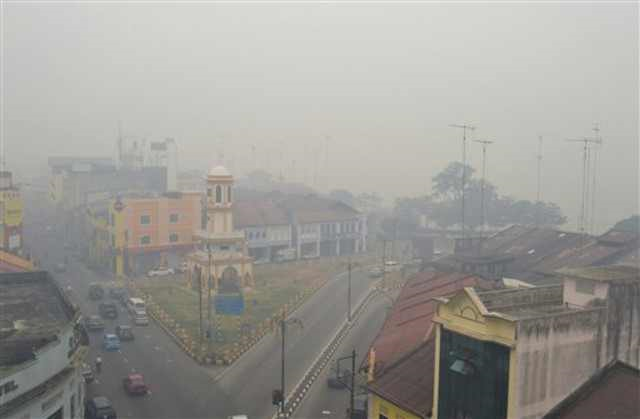Motorists make their way through a town covered with a thick haze in Muar, northwestern Johor, Malaysia, on 22 June 2013.  Malaysian authorities are declaring a state of emergency in the southern district of Muar where a smoky haze blamed on Indonesian forest fires has triggered one of the country's worst pollution levels. Photo: AP