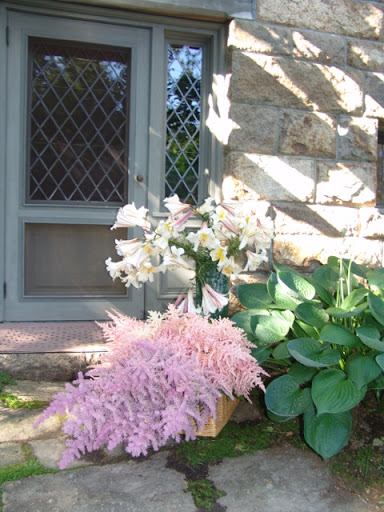 Astilbe and trumpet lilies waiting to be arranged outside the door of the flower room.