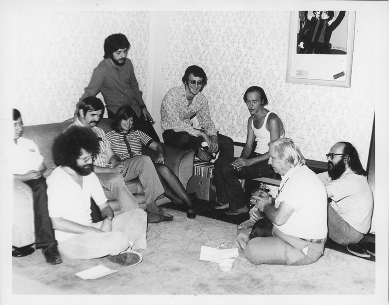 A Gay Community Services Center meeting including Don Kilhefner (far right), Morris Kight (second from right), Jim Kepner (moustache), June Herrle (woman on couch), and John Platania (sitting on floor in front of Kepner). 1971.