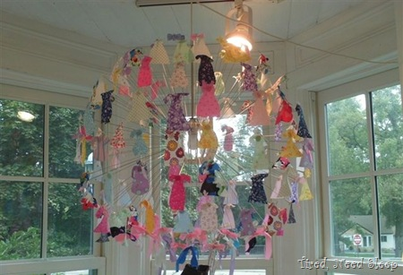 hanging artwork made up of fabric pieces cut to look like clothing