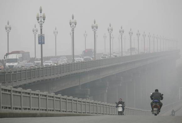People ride along a bridge on a smoggy day in Nanjing, Jiangsu province, 18 January 2014. Photo: Reuters / China Daily