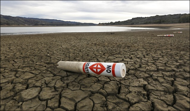 In this 4 February 2014 file photo, a warning buoy sits on the dry, cracked bed of Lake Mendocino near Ukiah, California. Natural variability alone cannot explain the extreme weather pattern that has driven both the record-setting California drought and the cooler weather seen in the Midwest and East this winter, a NASA study finds. Photo: Rich Pedroncelli / AP