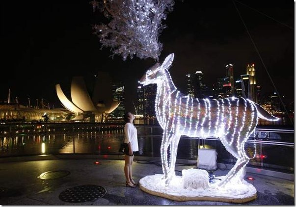 a-tourist-looks-at-a-reindeer-display-lit-up-in-preparation-for-christmas-celebrations-in-front-of-the-skyline-of-the-finan599x0