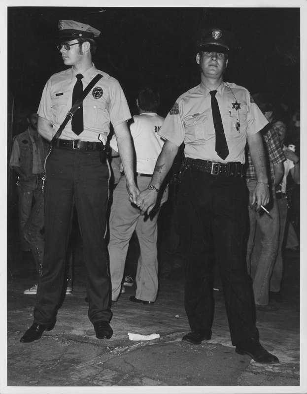 Police officers holding hands at the Los Angeles Christopher Street West pride parade. 1972.