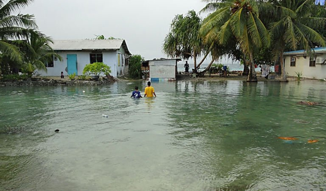 Two local residents wade through flooding caused by high ocean tides in low-lying parts of Majuro Atoll, the capital of the Marshall Islands. Extreme high tides have flooded parts of the low-lying Marshall Islands capital Majuro with a warning Sunday of worse to come because of rising sea levels. physorg.com