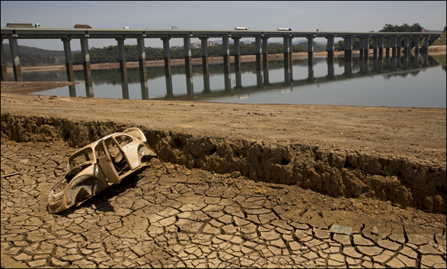 The frame of a car on the cracked earth at the bottom of the Atibainha dam, part of the Cantareira system near São Paulo, Brazil, in October 2014. Photo: Andre Penner / AP