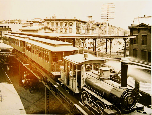 c.1885 view of a S/B Metropolitan 2nd Ave El three car monitor roof car train at the Chatham Square South platform being hauled by a brand new Forney locomotive #298. The second car has the distinctive Metropolitan Elevated Railway window pattern. The monitor roof cars were delivered to the Metropolitan 6th Ave El in 1878. The monitor roof cars were either rebuilt with a standard RR roof or replaced some time later and survived as trailers until the end of 6th Ave El operation in 1938. This view is looking East over the platform out to East Broadway.