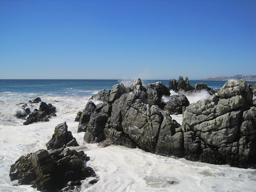 Big waves crashing on a rocky section.