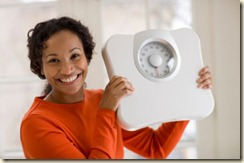 Happy Black woman holding scale