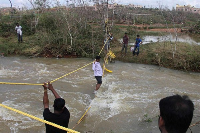 People use a rope bridge to cross floodwaters on 26 October 2013 in Ganjam district in eastern India. Photo: Reuters