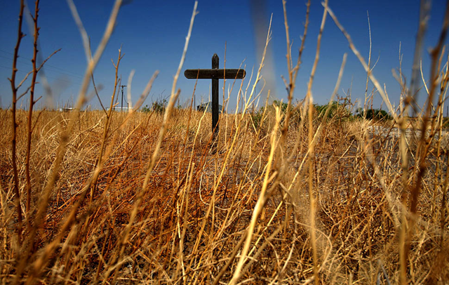 Verhalen, Texas — Dry weeds surround a wooden cross in a field near the town of Verhalen, 21 May 2011. The state is suffering from a severe drought that is causing wildfires and hardship for ranchers and farmers. PHOTOGRAPH BY: Genaro Molina / Los Angeles Times