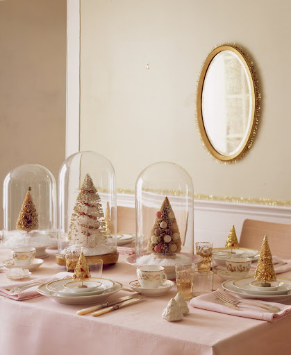 Ornamented and gilded brush trees provide the theme for a holiday table and complement the glistening trim on the dishware. The 1960s trees beneath the glass are highly sought, running $100 and up.
