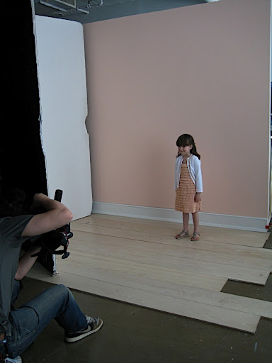 Nico on set, modeling the sequin cardigan.
